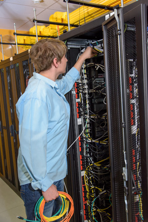 Young male IT specialist connecting network cable to server patch panel in datacenter
