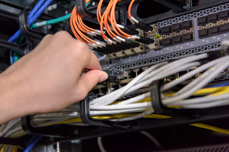Hand connecting network cable to server patch panel in datacenter