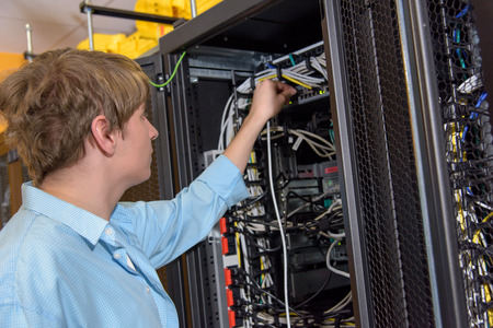 patch panel: Datacenter manager connecting network cable to server patch panel