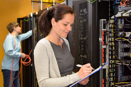 tecnologia informacion: Mujer que ingeniero en la sala de servidores de red de cheques Foto de archivo