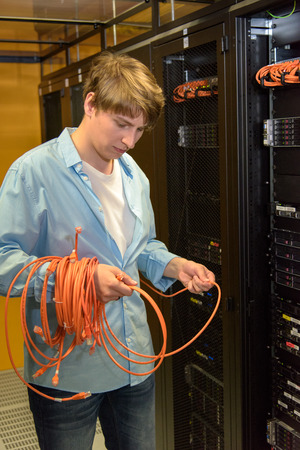 Datacenter professional checking network cables by server racks Stock Photo