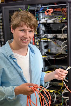 Jeune technicien tenant câble optique en datacenter en face rack ouvert des serveurs de réseau