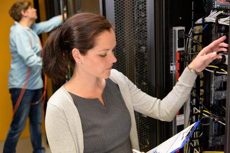 Vrouw datacenter manager in serverruimte controle netwerkverbindingen Stockfoto