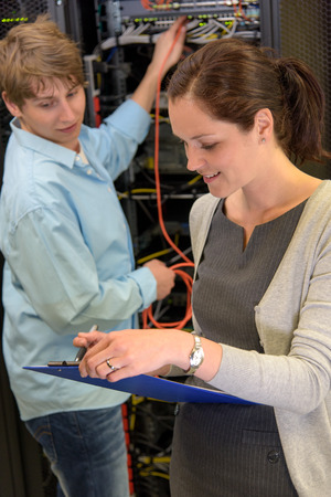 Two datacenter professionals checking servers in climate controlled room Stock Photo
