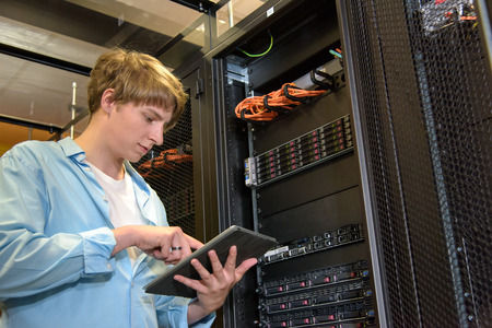 IT specialist configuring servers in climate controlled datacenter