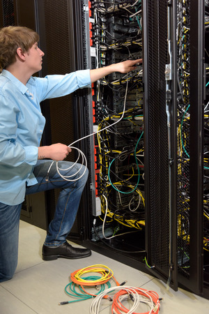 Datacenter manager working on server with network cables