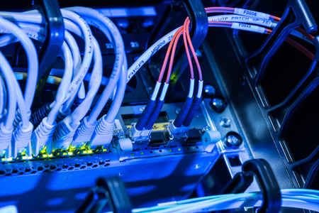 Fiber optic cables in network switch of datacenter Stock Photo