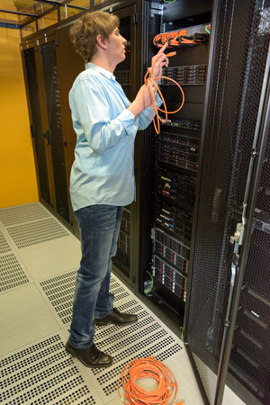 Datacenter professional in climate controlled server room checking network cables