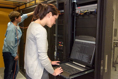 Female technician in server room checking network security with laptop photo