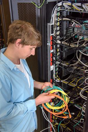 Ingénieur Datacenter avec des câbles de réseau dans l'avant du rack ouvert avec les serveurs de réseau et les panneaux de brassage