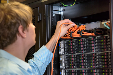 ful: IT specialist patching network wire in rack ful of server hardware Stock Photo