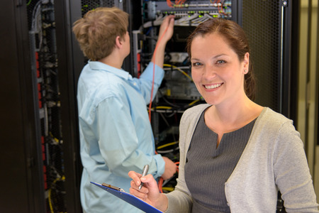 Two network engineers in server room checking computers photo