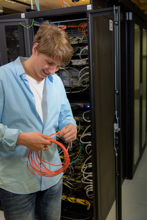 Datacenter specialist working with optical cable with racks of servers in background