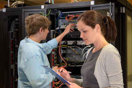 Team of IT specialists in datacenter working by network servers photo