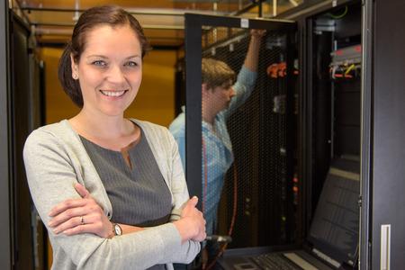 Encargado de sexo femenino del centro de datos con su colega en la sala de servidores