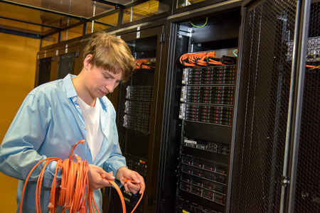 Datacenter engineer rolling up network cables by rack full of network servers