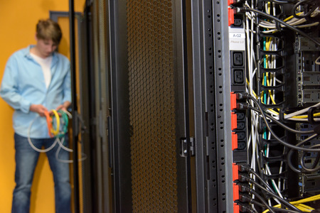 Datacenter power sockets with engineer working with server network wires in background