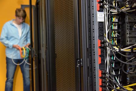 Prises de courant avec Datacenter ingénieur travaillant avec les câbles réseau du serveur en arrière-plan