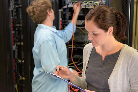 Équipe de technicien de réseau datacenter vérifier la sécurité sur les serveurs