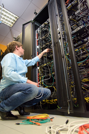 IT specialist installing cables in datacenter by open rack of patch panels