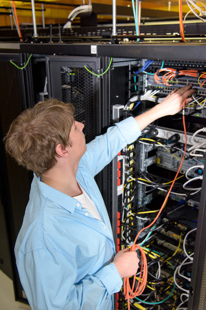 Datacenter technician patching optical cable in network server Stock Photo