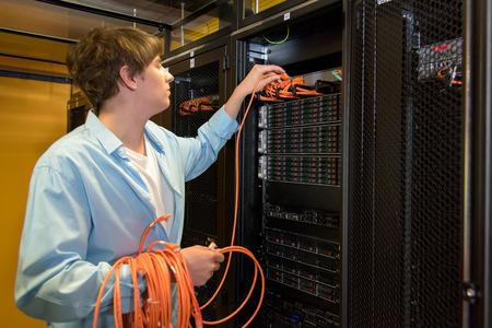 Datacenter technical manager patch cables in rack full of network server harddisks