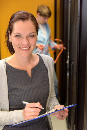 Business woman in server room checking network status