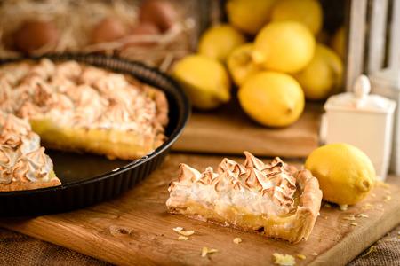 French lemon meringue pie slice on wooden plank