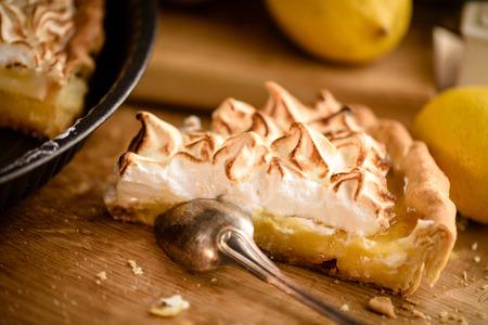 Slice of lemon meringue tart with silver spoon on wooden cutting board Stock Photo
