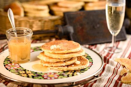 Gaufres avec du miel dans la plaque traditionnelle et verre de champagne