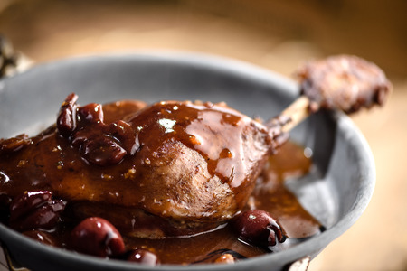 gastronomy: Roasted duck leg covered with red port wine cherry sauce in tin plate Stock Photo
