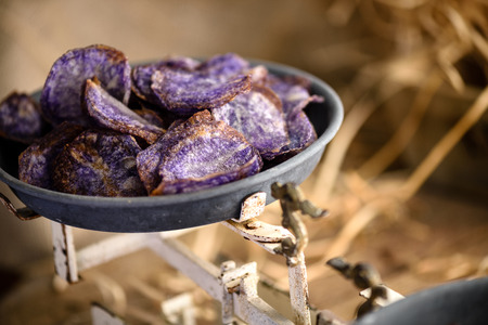 Sweet potato purple chips in tin plate of old scale Stock Photo