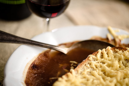 Spoon in french onion soup with cheese and bread croutons