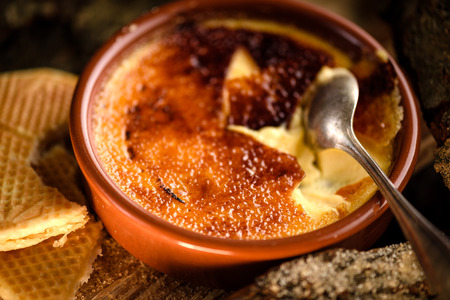 Traditional french creme brulee dessert with caramel sugar cracked by spoon