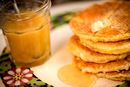 Gaufres avec du sirop de miel et pot de miel en verre