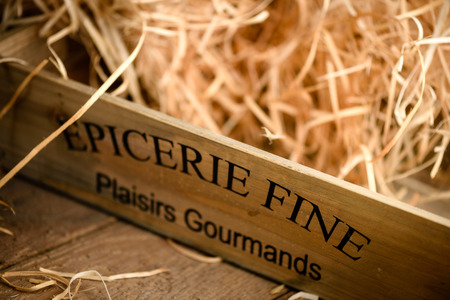 french text: Wooden crate filled with straw with french text printed Stock Photo