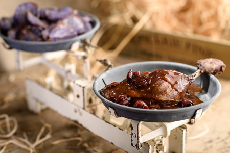 Roasted duck leg in port wine cherry sauce with sweet purple potatoes chips