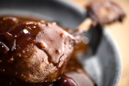 Rôti cuisse de canard recouvert de porto rouge sauce vin de cerise dans la plaque d'étain
