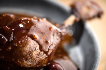 Roasted duck leg covered with red port wine cherry sauce in tin plate Stock Photo