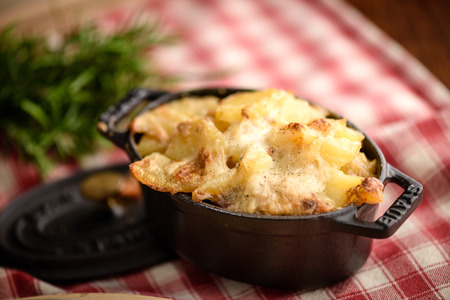 Potato gratin dauphinois in traditional french ceramic pan on rustic tablecloth