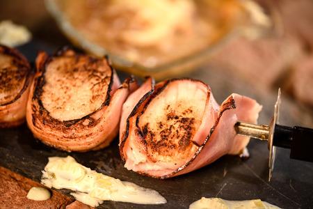 Brochette de pétoncles grillés enveloppés dans du jambon avec sauce au vin blanc