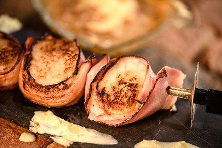Skewer of grilled scallops wrapped in ham with white wine sauce