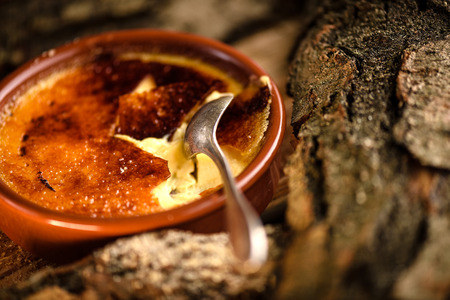 brulee: French creme brulee cracked caramel sugar topping by spoon