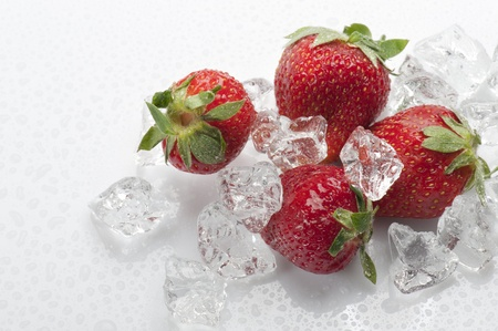 frozen strawberries with ice cubes, on white background