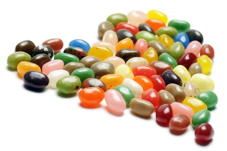 fruit jelly beans, heart-shaped on white background