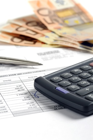 euro bill: checking bank account with calculator and pen