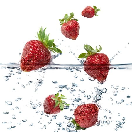 strawberries splash in transparent water, on white background photo