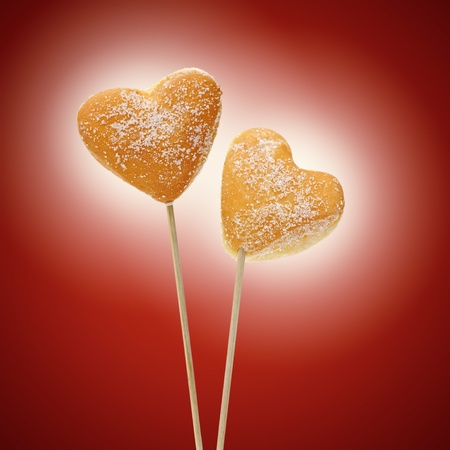 donuts heart-shaped inserted on sticks, on red background photo