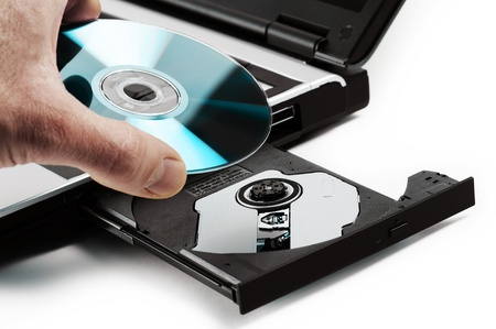 optical instrument: compact disk inserted on notebook drive, on white background Stock Photo
