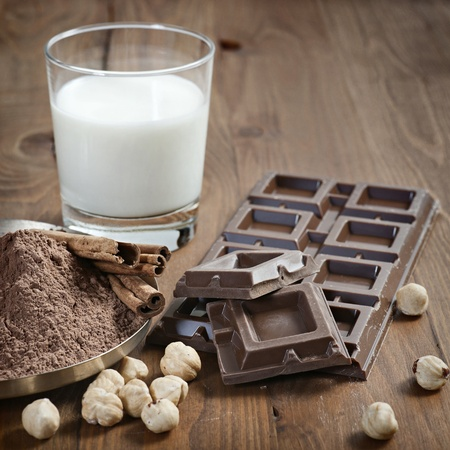 endorphines: chocolate bar with cocoa powder, cinnamon, nuts and milk on wood background Stock Photo